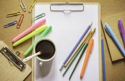 Artigos de papelaria: prancheta, grampos, lápis, penas da cor, pincel, Fotos de Stock Royalty Free