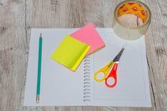 Artigos de papelaria: tesouras, fita, pena, lápis e caderno em uma tabela de madeira fotografia de stock