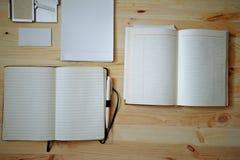 Artigos de papelaria vazios ajustados no fundo de madeira velho: cartões, brochura, caderno, bloco de notas e pena Estilo do vint Imagens de Stock Royalty Free