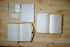 Artigos de papelaria vazios ajustados no fundo de madeira velho: cartões, brochura, caderno, bloco de notas e pena Estilo do vint Imagem de Stock