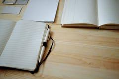 Artigos de papelaria vazios ajustados no fundo de madeira velho: cartões, brochura, caderno, bloco de notas e pena Estilo do vint Fotografia de Stock