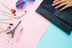 Artigos do cosmético e da forma com a mulher que guarda o saco de embreagem da forma fotografia de stock