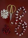 Artigos para fazer uma festão do arando e da pipoca em uma tabela vermelha Imagens de Stock Royalty Free