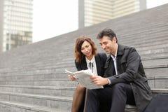 artikel van de ingenieurs het mannelijke en vrouwelijke lezing over bedrijf binnen stock afbeelding
