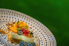 Artikeln med ensamrätt italien pannacottaen med mangosorbet och frukt som tjänas som på plattan, modern gastronomi, sommarefterrä royaltyfri foto