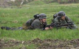 Artilheiro alemão do soldado de infantaria e de máquina com uma metralhadora que encontra-se na grama Reconstrução do episódio do Imagens de Stock