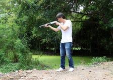 Artilleristmannen som står det långa vapnet som rätt från sidan siktar med vit skjorta- och grov bomullstvilljean royaltyfria bilder