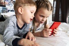 Artilugios de los niños: el muchacho es miradas escépticas en el smartphone a la muchacha Ambos mienten en la cama foto de archivo