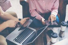 Artilugios electrónicos de Team Analyze Finance Online Report de los compañeros de trabajo jovenes Proyecto de lanzamiento de Bus Imagen de archivo libre de regalías