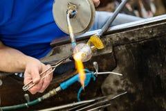 Artis värmer den exponeringsglas gjorda seagullstatyn genom att använda gass för en acetylen till arkivfoton