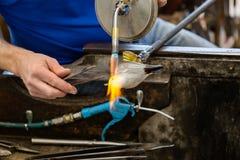 Artis värmer den exponeringsglas gjorda seagullstatyn genom att använda gass för en acetylen till royaltyfri foto