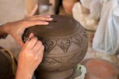 Artisan's remet des modèles de gravure sur le pot d'argile dans l'atelier, production asiatique traditionnelle de poterie de te Image stock