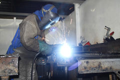Artisan arc welding. Sparks flying from a factory artisan wearing protective gear while welding metal Stock Images
