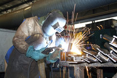 Artisan arc welding. Sparks flying from a factory artisan wearing protective gear while welding metal Royalty Free Stock Photography