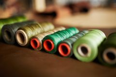 Artisan Atelier. Close up shot of green thread spools lying in textiles in atelier, copy space royalty free stock image