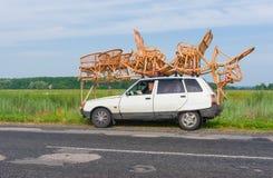 Artisan ayant une petite pause tandis que vannerie de transport sur un toit d'une petite voiture Photos libres de droits