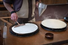 Baker`s hands pouring sweet on the griddle for the sweet crepe`s preparations. Artisan Baker working in the bakery in the crepes preparations royalty free stock images