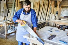Artisan barbu Sawing Wooden Board images libres de droits