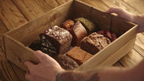 Artisan bread bakery presentation set. Baker with tattooed hands puts rustic wooden box with different types of healthy breads on vintage farm table to present stock video