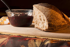 Artisan Bread. Bread and Jam with table setting on bamboo cutting board. Fall napkin in background stock images