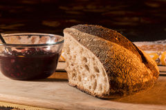 Artisan Bread. Bread and Jam with table setting on bamboo cutting board. Fall napkin in background royalty free stock photography