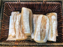 Artisan Bread Loaves. Artisan white bread loaves, dusted with flour, in a cane basket, for sale at a food shop royalty free stock photos