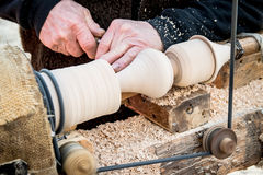 An artisan carves a piece of wood using a manual lathe. Stock Photos