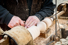 An artisan carves a piece of wood using a manual lathe. Royalty Free Stock Images