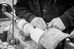 An artisan carves a piece of wood using a manual lathe. Royalty Free Stock Image