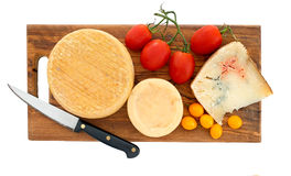 Artisan cheeses on board with red and yellow tomatoes. Genuine farm produced organic cheese, made with raw cows milk. Includes blue cheese Stock Photos