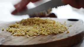 Artisan chef dicing almond confectionery on authentic chopping board stock footage