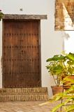 Artisan crafted wood door to a vintage hotel room in Spain. Artisan crafted wood door and frame in brick pateo area of a vintage hotel room in the old town of stock photo
