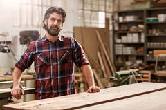 Artisan craftsman with a beard in his woodwork workshop Stock Photos