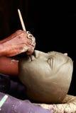 An artisan creates clay head of goddess Durga Stock Photos
