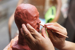 Artisan creating clay head. An artisan working on a clay idol head of traveller royalty free stock images