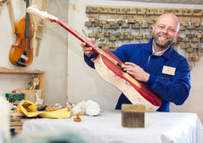 Artisan creating a guitar in workshop Stock Photography