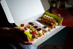 Artisan eclairs. A person holding out a box of artisan éclairs with fruit, meringue, coconut and chocolate topping Stock Photography
