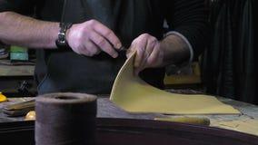Artisan en cuir de marchandises au travail dans son atelier banque de vidéos