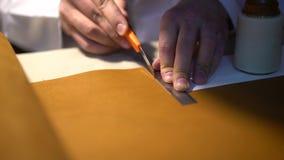 Artisan en cuir travaillant faisant des produits à la table dans le studio d'atelier banque de vidéos