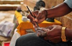Artisan faisant le foyer en pierre de découpages sur des mains Photos libres de droits