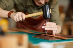 Artisan Forming Leather. Close up of woman artisan making leather belt in leatherworking shop , copy space stock images
