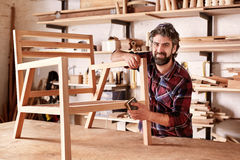 Artisan furniture designer sanding a chair in his workshop Royalty Free Stock Images