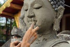 Artisan hands making clay buddha Royalty Free Stock Photo