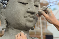 Artisan hands making clay buddha Stock Images