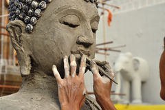 Artisan hands making clay buddha Royalty Free Stock Image