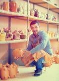 Artisan having ceramics in hands. Happy mature male potter taking ceramics in hands in workshop stock photo