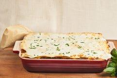 Artisan homemade baked lasagna. Artisan, organic homemade baked lasagna in a red heat resistant rectangular baking dish with basil and a chunck of mozzarella Royalty Free Stock Photo