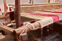 Artisan loom in wood. Picture of Handmade loom with red threads in wood royalty free stock image