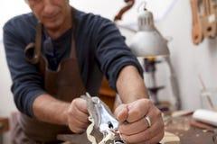 Artisan lutemaker working a violin Stock Image