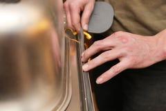 Artisan mettant la garniture sur le bassin de cuisine Photos libres de droits